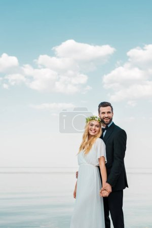 smiling wedding couple in suit and white dress holding hands on beach