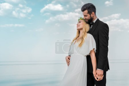 wedding couple in suit and white dress hugging on beach