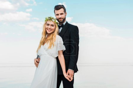 wedding couple in suit and white dress holding hands and looking at camera on beach