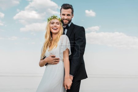 laughing wedding couple in suit and white dress holding hands and looking at camera on beach