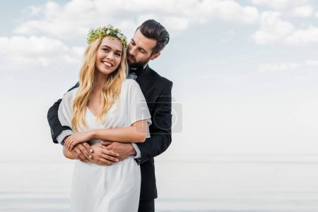 Photo for Handsome groom in suit hugging attractive bride on beach - Royalty Free Image