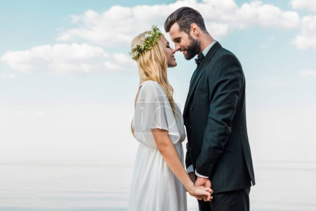 wedding couple in suit and white dress holding hands and touching with noses on beach