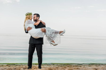 handsome groom in suit holding attractive bride in white dress on beach