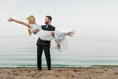 handsome groom in suit holding attractive smiling bride in white dress on beach
