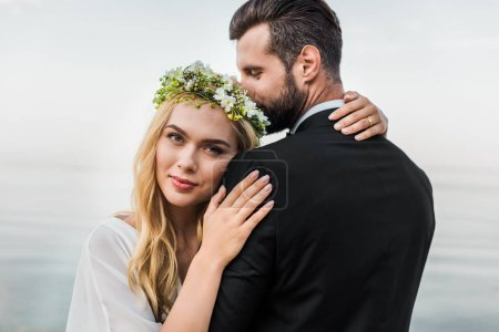 attractive bride in wreath and groom in suit cuddling on beach