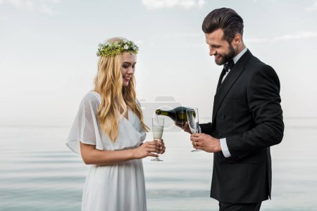 handsome groom pouring champagne into glasses on beach