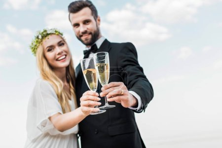 selective focus of wedding couple clinking with glasses of champagne on beach
