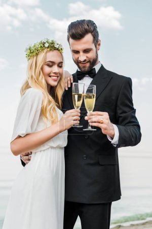 smiling wedding couple clinking with glasses of champagne on beach