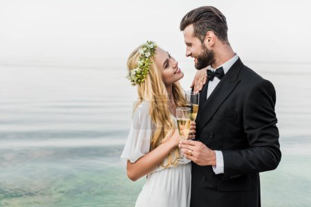 wedding couple holding glasses of champagne and looking at each other on beach