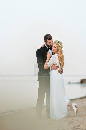 Photo for Wedding couple cuddling on sandy beach near ocean - Royalty Free Image
