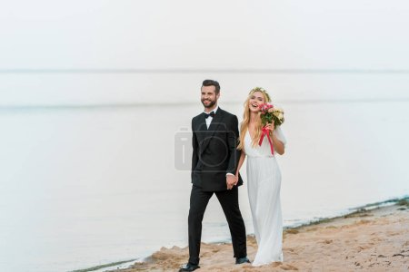 smiling wedding couple holding hands and walking on beach
