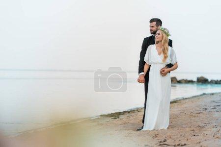 handsome groom in suit hugging attractive bride in white dress on beach