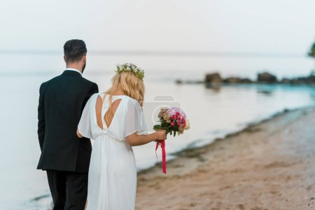 back view of wedding couple with bouquet walking on beach