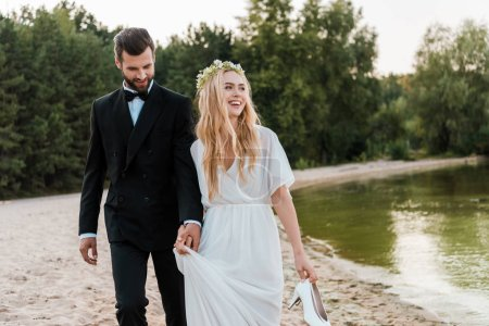 wedding couple holding hands and walking on beach, laughing bride holding high heels in hand