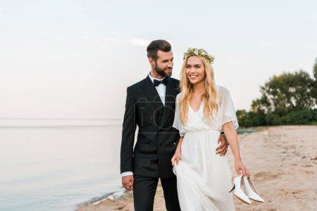 groom hugging bride and walking on beach, bride holding high heels in hand