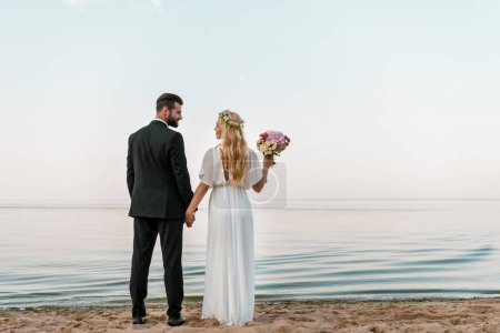 back view of wedding couple standing on beach with wedding bouquet and looking at each other