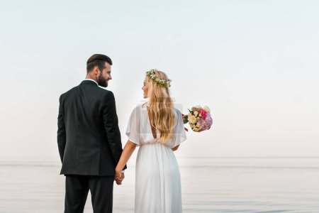 back view of wedding couple standing on beach, holding hands and looking at each other