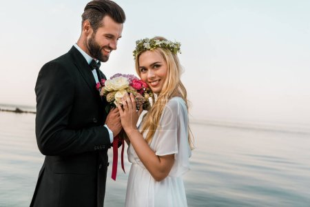 side view of wedding couple standing with bouquet on beach, smiling bride looking at camera