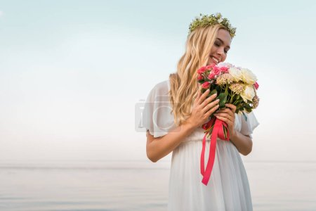 smiling attractive bride in white dress and wreath looking at wedding bouquet on beach