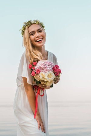 laughing attractive bride in white dress and wreath holding wedding bouquet on beach and looking at camera