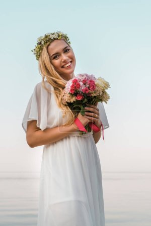 smiling beautiful bride in white dress and wreath holding wedding bouquet on beach and looking at camera
