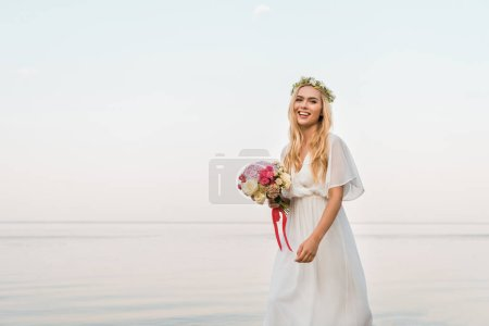 smiling attractive bride in white dress and wreath holding wedding bouquet and walking near sea