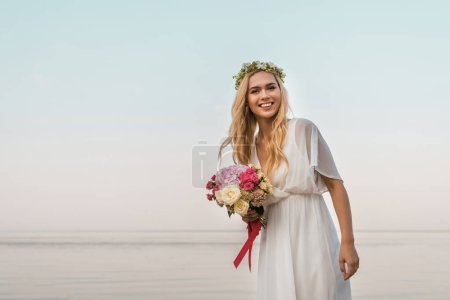 smiling attractive bride in white dress and wreath holding wedding bouquet of roses and looking at camera on beach