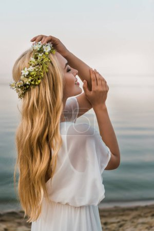 side view of attractive bride in white dress and wreath of flowers standing with closed eyes on beach
