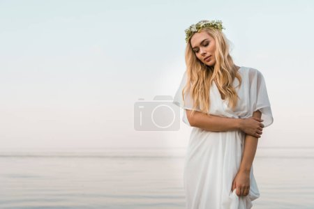 attractive bride in white dress and wreath of flowers hugging herself near ocean