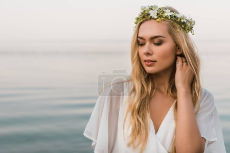 attractive bride in white dress and wreath of flowers touching hair on beach