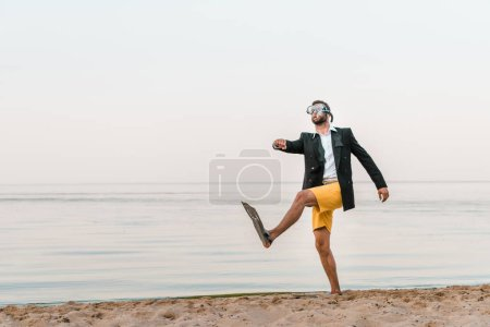 man in black jacket and shorts walking with swimming mask and flippers on sandy beach