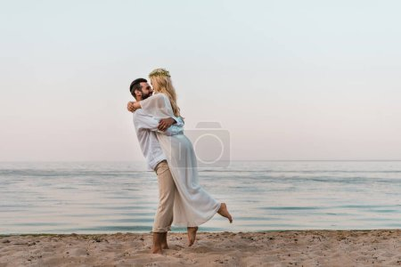 bride in white dress and groom cuddling on beach