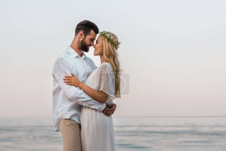 side view of bride and groom hugging and touching with noses on beach