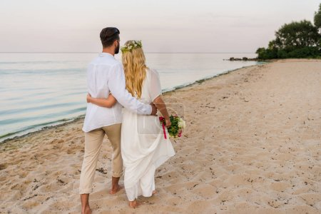 rear view of bride and groom hugging and walking on beach