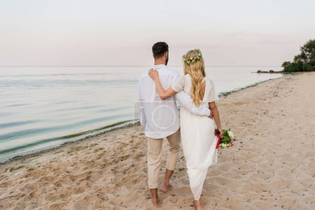 rear view of bride with wedding bouquet and groom hugging and walking on beach