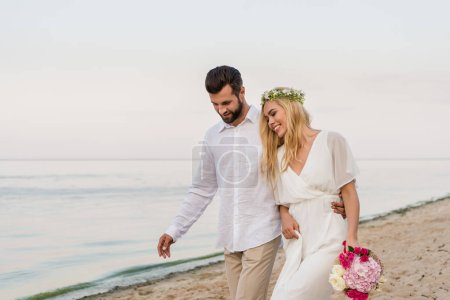 handsome groom hugging beautiful bride with wedding bouquet and they walking on beach