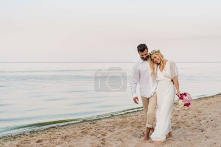 handsome groom hugging smiling bride with wedding bouquet and they walking on beach
