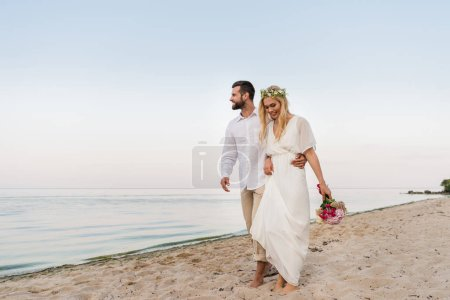 handsome groom hugging beautiful bride with wedding bouquet and they walking on seashore