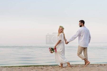 happy bride and groom holding hands and walking with wedding bouquet on beach