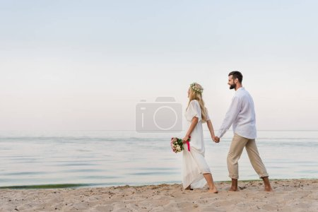 side view of bride and groom holding hands and walking with wedding bouquet on beach