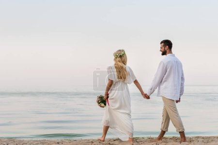 back view of bride and groom holding hands and walking with wedding bouquet on beach