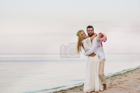 happy bride and groom hugging on beach and holding wedding bouquet