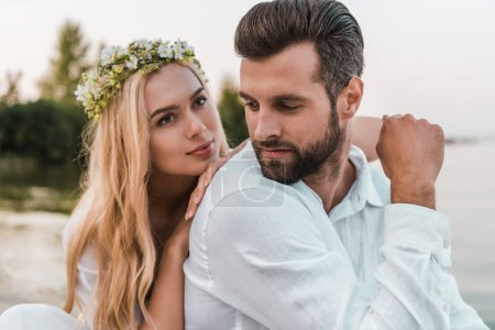 portrait of beautiful bride in wreath and handsome groom on beach