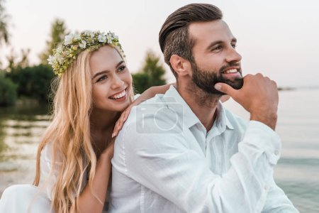 portrait of smiling bride in wreath and handsome groom on beach
