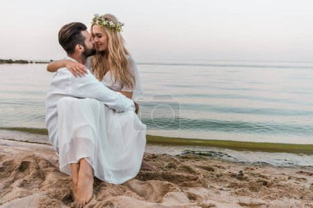 affectionate bride and groom going to kiss on beach