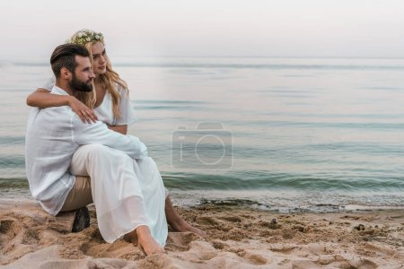 elegant groom and bride sitting on log on beach and looking away