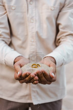 Photo for Cropped image of groom holding wedding rings with sand in hands on beach - Royalty Free Image