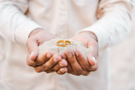 Photo for Cropped image of groom holding wedding golden rings with sand in hands on beach - Royalty Free Image