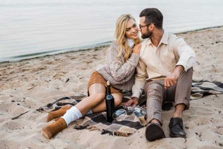 stylish couple in autumn outfit looking at each other on beach with bottle of red wine