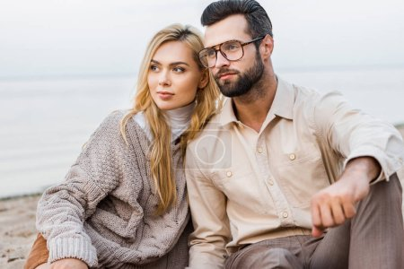 stylish couple in autumn outfit sitting on beach and looking away